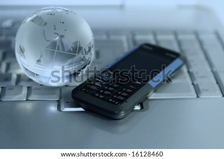 Blue tinted image of cellular and glass globe on laptop keyboard. Narrow DOF. Focus on mobile phone buttons
