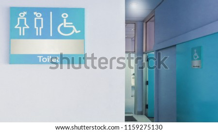 Blue toilet sign in front of toilet room or rest room with man, woman and handicap icon set  symbol on white concrete wall background, modern, hygiene and clean restroom concept #1159275130