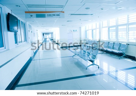 blue tone of hospital waiting room with empty chairs.