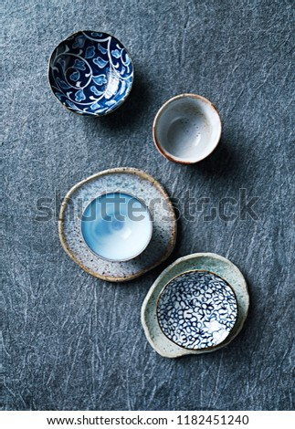 Blue toned ceramic dishware on indigo cloth. Flat lay.  Hand crafted ceramic. Copy space