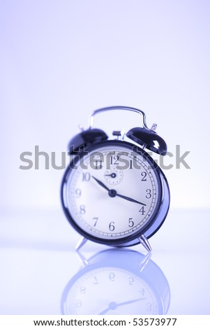 Blue toned image of a classic alarm clock, selective focus