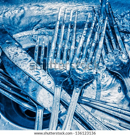 Blue toned image of forks and knives washed on a kitchen sink with a splash of water