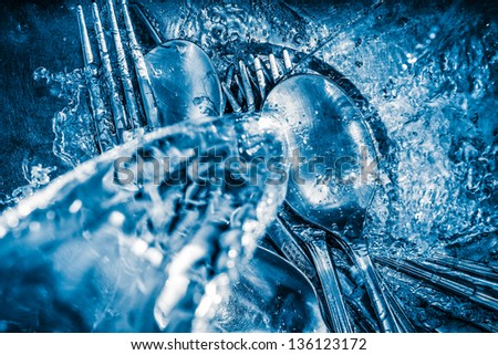 Blue toned image of metallic silverware being washed on a sink with a splash of water