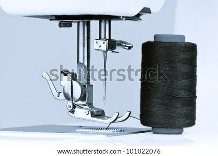 Blue toned macro image of a sewing machine and reels with thread