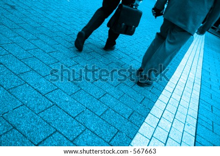 Blue toned photo of two business men walking, highly saturated