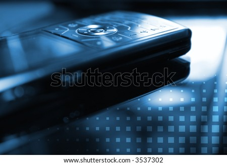 Blue toned picture of a mobile phone (shallow DoF, focused on round central button) - stock photo