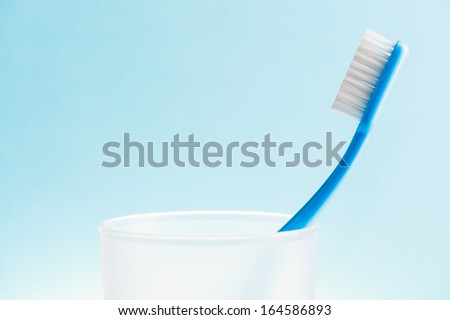 Blue toothbrush in white plastic glass over blue background.