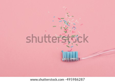 blue toothbrush on pink background with sprinkles. minimal pastel flat lay fashion style. #495986287