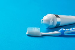 Blue toothbrush with silicone bristles and a tube of toothpaste on a blue background. Means to care for the oral cavity.