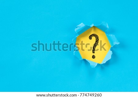 blue torn paper revealing question mark symbol on yellow paper. question mark background