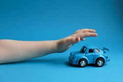 Blue toy car on a blue background and a children's hand that wants to take it