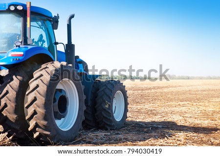 Blue tractor on the background of an empty field and a clear blue sky #794030419