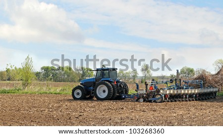 Blue tractor pulling a planter planting corn