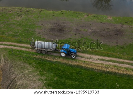 Blue tractor pulling a tank, on an unpaved road #1395919733