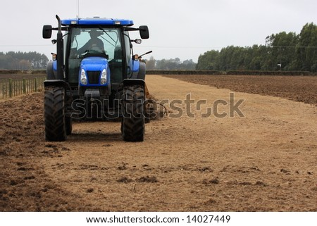Blue tractor using shallow cultivation tillage on a paddock in Canterbury, New Zealand