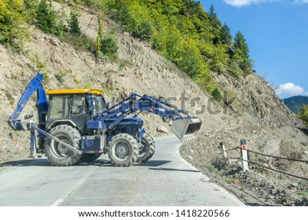 Blue tractor works on asphalt road in mountains, trying to fix, reach red white boundaries columns along highway - beware dangerous construction works with closing all road #1418220566