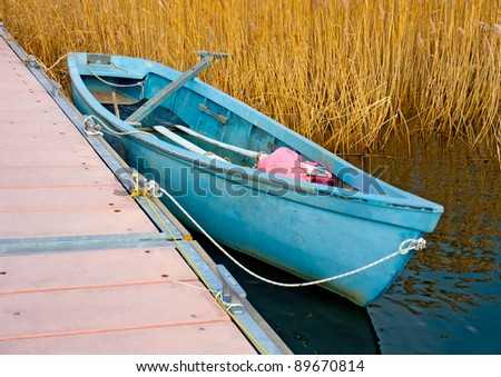 Blue traditional old wooden fishing boat in the lake Prespa near Psarades village in northern Greece