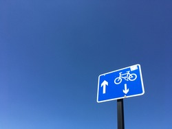 Blue traffic sign with a bicycle and two arrows pointing in opposite directions for bike lane with cloudless blue sky as background  with copy space for runaround or wraparound text