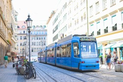 Blue tram on shopping street in Munich Germany with blurry people