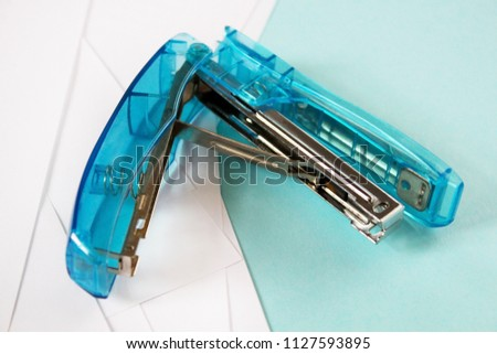 Blue transparent stapler for binding sheets of paper closeup. Office equipment for use in documentation, blue background. Stationery for business concept. Opening big blue stapler with metal staple.