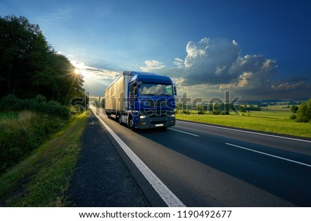 Blue truck arriving on the asphalt road in rural landscape in the rays of the sunset