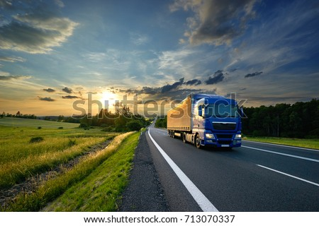 Blue truck driving on the asphalt road in rural landscape at sunset