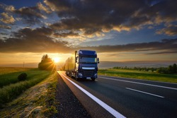 Blue truck driving on the asphalt road in rural landscape at sunset between dark clouds