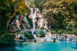 Blue turquoise water pond Kuang Si waterfall among rain forest in Luang Prabang, Laos during summer season.