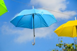 Blue umbrella hanging in the air, decorate the place with colorful umbrellas