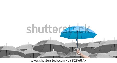 Blue umbrella over dark umbrellas on white background. The difference to step up to leadership in business.hand of man holding a blue umbrella in raining. side view. #599296877