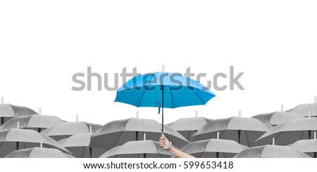 Blue umbrella over dark umbrellas on white background. The difference to step up to leadership in business.hand of man holding a blue umbrella in raining. side view.