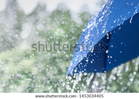 Blue umbrella under heavy rain against nature background. Rainy weather concept.