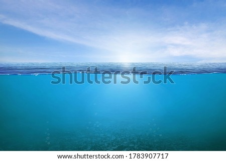BLUE UNDER WATER waves and bubbles. Beautiful white clouds on blue sky over calm sea with sunlight reflection, Tranquil sea harmony of calm water surface. Sunny sky and calm blue ocean.