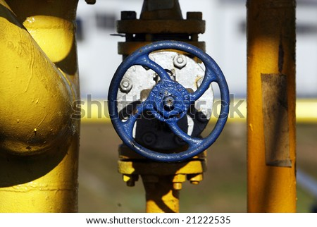Blue valve on yellow gas pipe at refinery