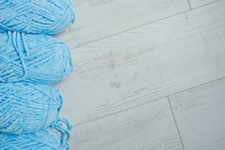 Blue velour yarn hanks on white wooden planks texture with much free space. Concept of creative hobby materials.