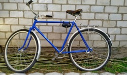 Blue vintage bicycle on a white brick wall background. Mobile photo