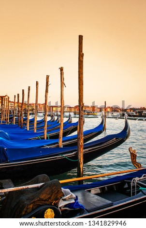 Blue vintage gondolas docked at the pier the Piazza San Marco in Venice, Italy during sunset