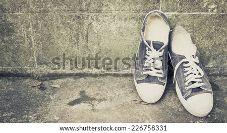 blue vintage shoes lean on old aged wall / concept \