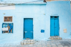Blue wall of old building and two painted doors and one window. Tunisia. Horizontal color photography.