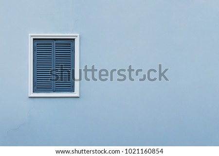 Blue wall of the house with a closed window left and details. #1021160854