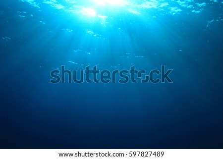 Blue water background and sunlight underwater #597827489