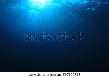 Blue water background and sunlight underwater #597827513