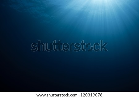 Blue water background with sun rays.