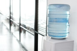 blue water gallon on electric water cooler in office area