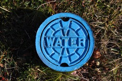 Blue water meter manhole on the grass