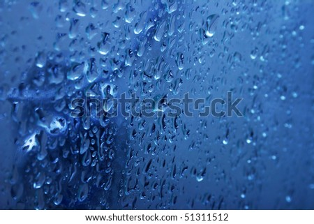 Blue water on glass door with bubbles as a background.