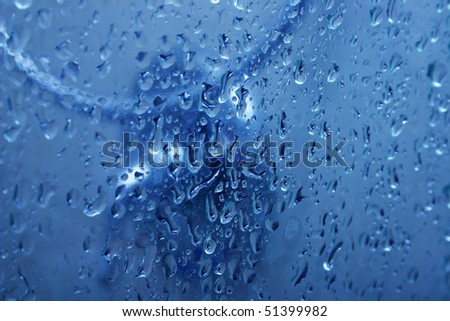 Blue water on glass shower door with bubbles as a background.