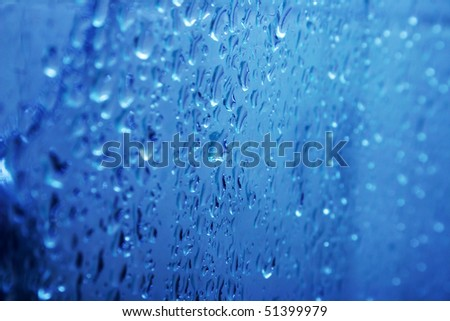 Blue water  on glass with bubbles as a background.