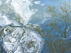 Blue water surface. Abstract reflection and abstract distorted tree branches in water. Distorted natural elements in the river.  Rippled water background. Layout or template of abstract