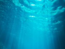 Blue water surface seen from under the water with some sunbeams drawing
